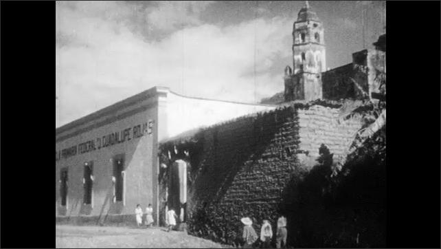 1930s: Children walk down street and through arch.  Church.  Boys sweep.  Children enter school.  Children sit in rows.  Teacher points to chalkboard.