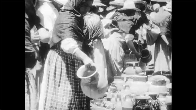 1930s: People walk through market.  Man carries food on head.  Woman sells hats.  People look at jars.  Children look at toys.