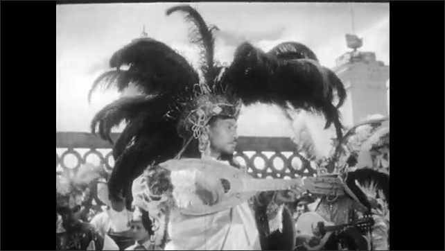 1930s: Girl picks up clay pig and pays man.  Man plays guitar.  Men dress in ceremonial costumes.