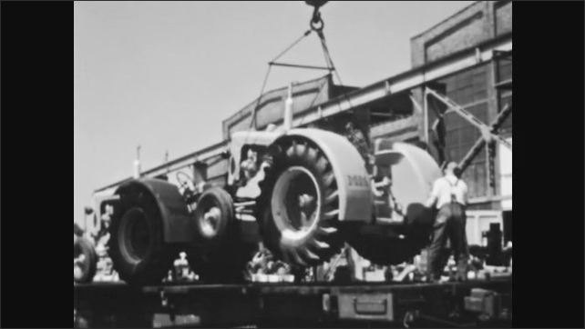 1940s: Tanker cars on tracks. Men load tractors onto flatbed cars. Freight train pulls out of railyard.