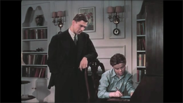 1930s: Boy sits at desk in living room, writes on paper. Man stands behind boy, leans on chair, talks. Boy stops writing, puts pencil in mouth, turns around, talks to man.