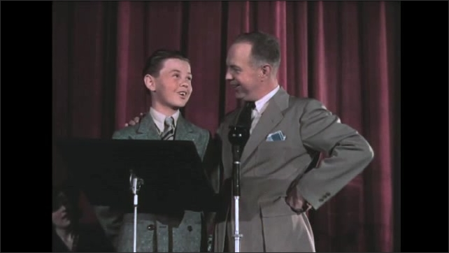 1930s: Man and boy stand at microphone and talk. Boy looks out at audience, man waves at boy.