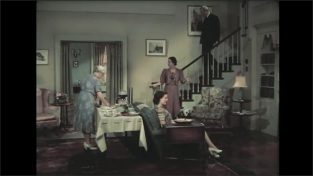 1930s: Woman sets tray down on table in living room, straightens coffee table. Old woman sets down tray on table. Man walks down stairs, talks.