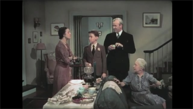 1930s: Family gathers in living room, man stands up, talks. Boy looks at table of food, talks. Woman and old woman talk. Woman sits on stool, looks sad, lets rings fall from her hand.