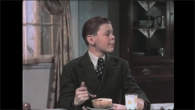 1930s: Family eat breakfast and talk at table. Boy holds spoon and speaks. Grandmother smiles and responds.