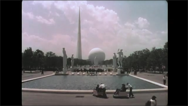 1930s: People walk along pavement near large flags. People observe large sphere, spire and fountains at World's Fair. People walk past and observe ornate statues.