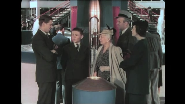 1930s: Man talks to family about exhibit. Family talks around time capsule display.