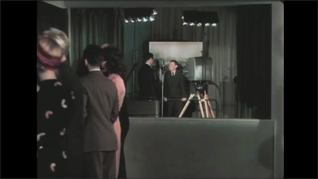 1930s: Boy straightens tie and talks into microphone. Men and women watch boy on small television outside studio. Father gives okay sign to boy in studio.