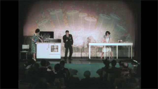 1930s: Wall sign with arrow. Announcer stands between woman washing dishes by hand and woman standing near automatic dishwasher. Crowd smiles. Announcer talks between women on stage.