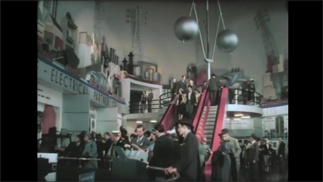 1930s: Crowds ride escalator and walk around displays in electronics exhibition hall. Large pendulum swings over stairs in exhibit hall.
