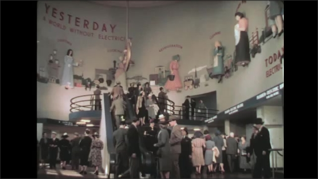 1930s: People walk around, ride up and down escalator, in the exhibit hall at the New York World's Fair.