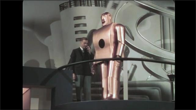 1930s: Women walk down stairs, join men and boy at bottom, watch presentation. Robot on balcony walks forward, man says stop, robot stops. Man turns robot, talks.