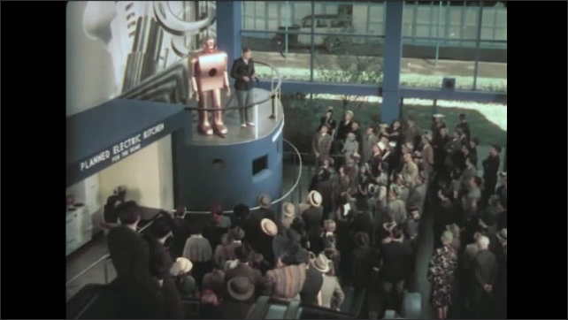 1930s: Man stands on high balcony next to robot, talks to crowd. Crowd watches from below. Man speaks into telephone, robot speaks.