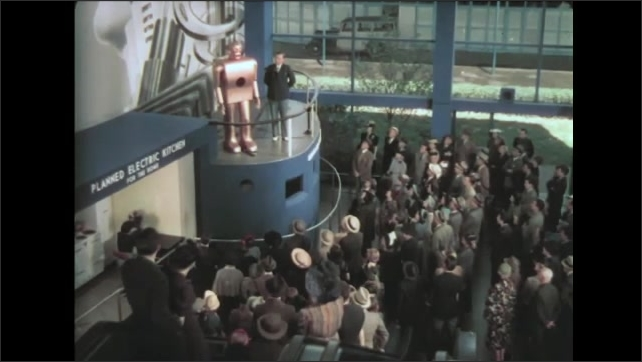 1930s: Man stands on high balcony next to robot, robot turns head and talks to crowd. Crowd watches from below.