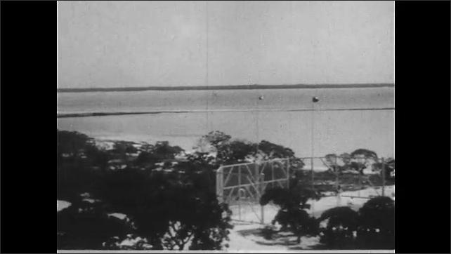 1940s: UNITED STATES: view across Wake Island landscape. Sea around coral island. Person walks on island.