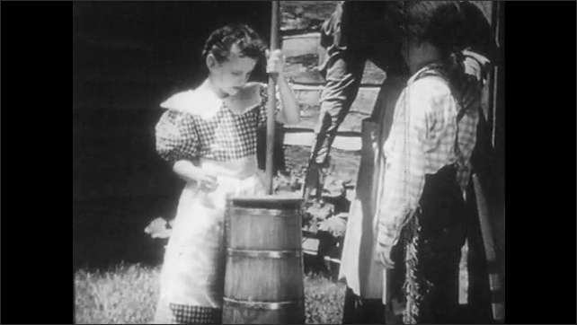 1950s: Woman pours cream into churn, places lid on top. Girl churns cream into butter, removes lid, scoops out butter.
