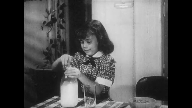 1950s: Woman walks out of cellar and into kitchen with pitcher. Family sits around table, woman places pitcher on table. Girl closes refrigerator, pours milk into glass. Milkman walks towards house.