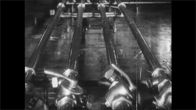 1950s: Man looks at gauges on machine, picks up telephone. Man turns valve on holding tank. Metal tubes. Pasteurizing machine.