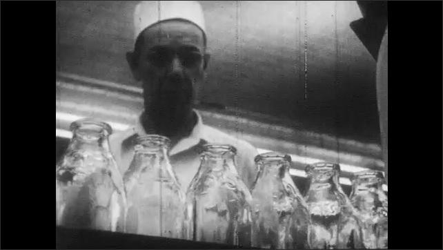 1950s: Empty milk bottles travel through machine, along conveyor belt. Man watches bottles. Machine fills bottles with milk, places caps on bottles.