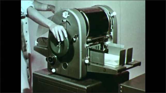 1950s: Woman turns off mimeograph, puts paper into machine. Hands roller paper through mimeograph.
