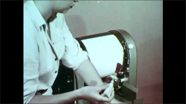 1950s: Woman puts stencil on mimeograph. Dissolve, woman paints ink on stencil.