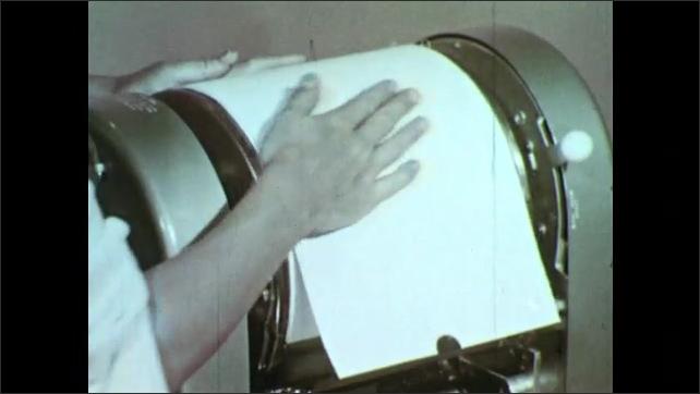 1950s: Hands press stencil onto mimeograph roller, pick up stencil.