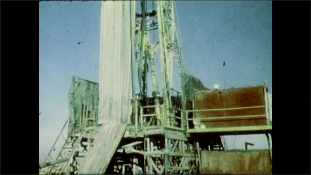1980s: UNITED STATES: workings of mine. Man works on mining platform on rig. Workers at mine. Men line up drill