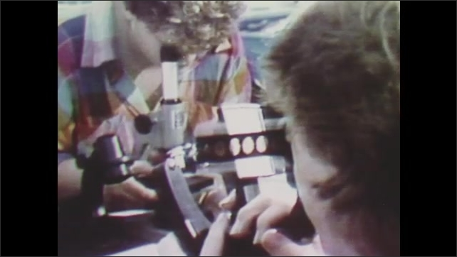 1970s: Students work in laboratory.  People look into microscopes.