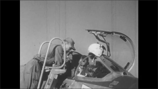 1960s: Man in military uniform speaks.  Man helps pilot prepare for takeoff.