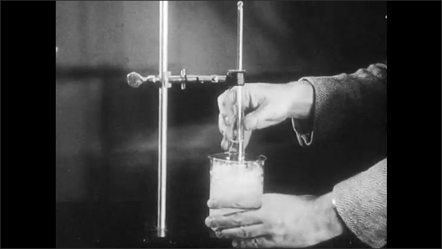 1960s: Hand points at test tube, then pushes beaker beneath tube. Hand adjusts knobs, then lowers tube half way into beaker. Hand uses stirrer to stir liquid in tube.