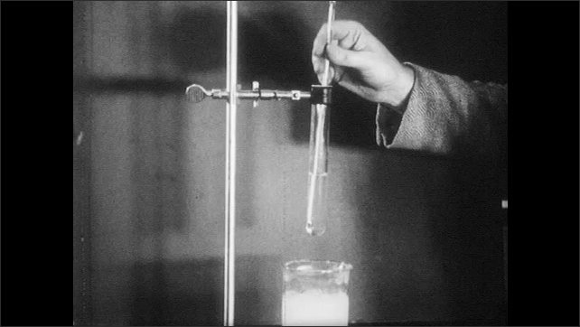 1960s: Hand stirs thermometer in test tube. Other hand stabilizes tube. Hands turn knob on metal clamp and lower test tube into liquid in beaker.