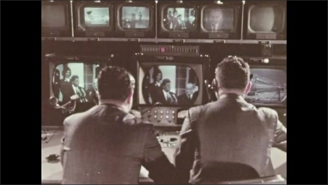1960s: Crowd by White House. Man by control panel. Men sitting by control panel, President Kennedy talking on monitors. People behind glass in control room. Close up of man. Men at control panel.