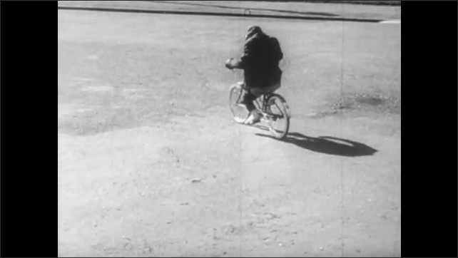 1940s: feet pedal bike, chimp on bike nearly runs into pedestrians in crosswalk, man climbs atop woman, man puts hand over eyes, makes goofy face, chimp rides bike in road, over sidewalk, into gate