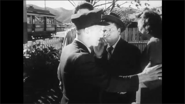 1940s: chimp in suit coat hides under bed, man and 2 women angrily talk with police officer, who walks up to chimp dressed as a woman on porch and shakes chimp's hand, they go inside house