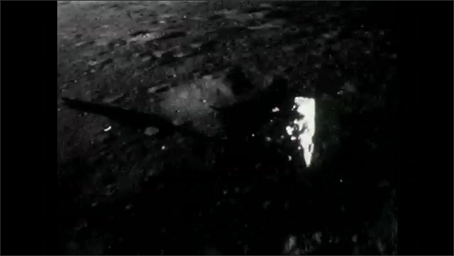1960s: Neil Armstrong holds a device and walks slowly on the moon. Astronaut turns around and walks slowly on the moon.