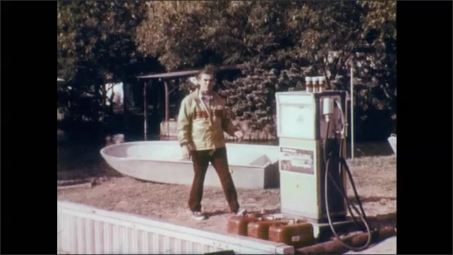 1970s: Man at harbor waves to boat of people, stands and begins speaking. Man continues to speak and rests arm on gas pump. Group of people on outboard powerboat speed through the water.