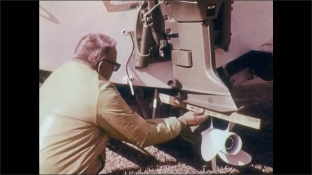 1970s: Boat on trailer. Man stands next to motor on boat, then measures motor in relation to body of boat with two rulers. Man unscrews sparkplug from motor.