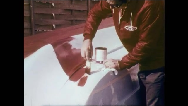 1970s: Man holds spark plug, uses instrument on it, rotates in hand. Man paints underside of boat red. Man uses socket wrench to tighten bolt on boat. Propeller, underside of motor. Man lifts motor.
