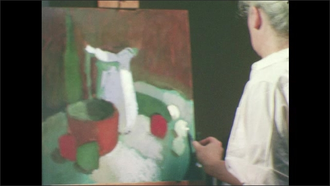 1950s: Woman stands at easel, paints still life with palette knife.