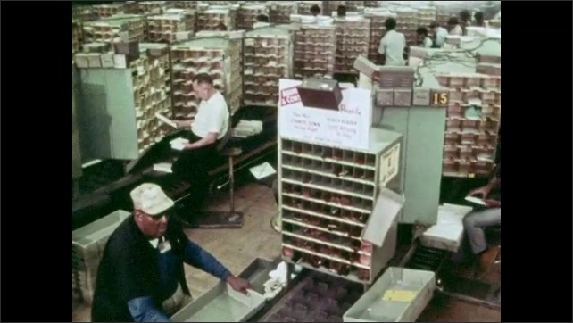 """1970s: Postal workers sort mail in a large work room. Titles read """"More????and louder."""""""