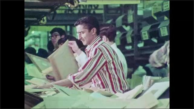 1970s: A bag of mail drops from a conveyor belt. Postal workers transport bags of mail around a busy facility. Workers sort through letters and packages.