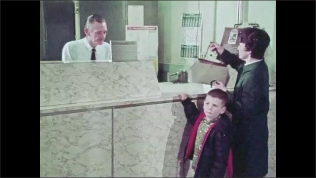 1970s: A mother and son walk up the steps and enter a post office. While the mother speaks to the teller, the boy looks around at the other customers and employees.