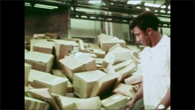 1970s: A postal worker rubber bands a pack of letters. A man presses buttons, monitoring operations at the post office on an array of screens. Workers and machines sort packages.