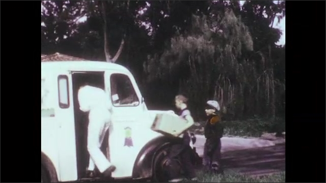 1950s: Man carries puppy down wooded path. Man carries dog to milk truck. Boys follow man with box. Man takes box from boys. Family sits on front stoop with puppy.