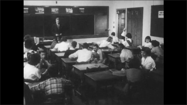 1950s: Teacher looks around class and flips through papers on desk. Students talk and settle into desks. Student rises and closes door. Teacher nervously speaks to class.