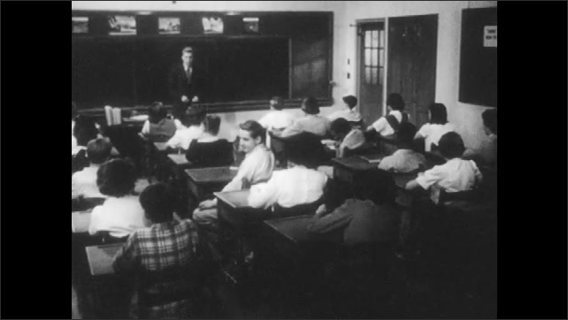 1950s: Teacher speaks to students in classroom. Arms on wall clock move.