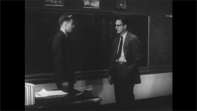 1950s: Man puts hands in pockets and speaks. Men talk near blackboard. Observer sits in desk and speaks to teacher. Teacher responds.
