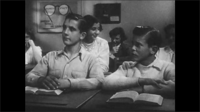 1950s: Teacher leans on back of chair and listens. Boys sit at desk and speak. Boys respond. Teacher hands note back to boys.