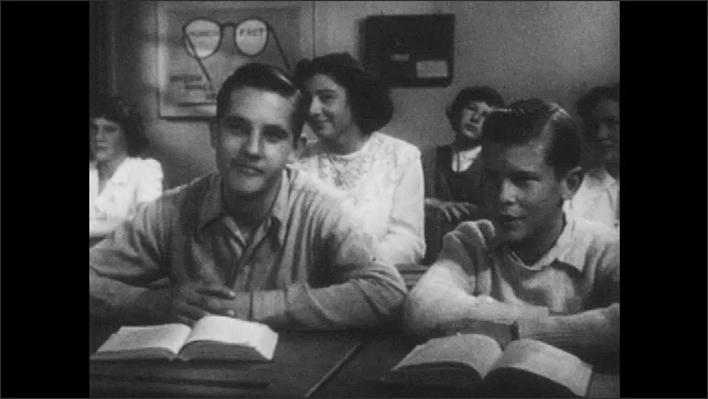1950s: Boys nudge each other and nod. Teacher draws on chalkboard and lectures class.