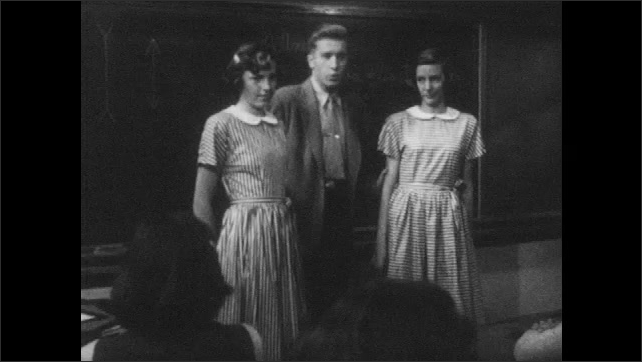 1950s: Teacher brings two girls to front of classroom and speaks. Man points to girls and speaks.